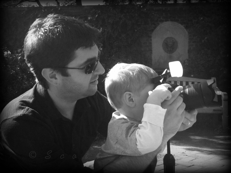 """Off To a Young Start!<br /> <br /> Daily Photos  -  November 15, 2011<br /> <br /> My 2 1/2 year old son and I. At first he was satisfied with only wanting to see the image previews on the cameras rear display. Then he became interested in how to actually take a picture. After showing him how to look through the viewfinder and where the shutter release button was, he felt that his abilities as a photographer had progressed beyond the need for my help, proclaiming in his little voice """"it's o-tay...my do it daddy!"""" Note the finger properly placed and at the ready on the shutter release! I can't help but smile, laugh and think 'that's my boy!'"""
