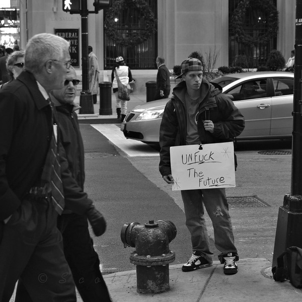"""""""Unf*ck the Future""""<br /> <br /> Daily Photos  -  December 5, 2011<br /> <br /> I've taken on a new adventure to explore street photography here in Chicago and this is the second posting from that series / genre. The purpose of this new adventure is to get out of my comfort zone and to challenge myself to capture various street scenes. This unposed and very fluid style of photography is a major departure from my """"standard"""" flower and landscape shots. I really like how the the first image in the series, Bell Ringer, captures the rawness of the street, but this second posting is so edgy that I was a little hesitant about sharing it...  <br /> <br /> This posting is of a young man who is part of the larger group of Occupy Chicago protesters who have taken up a permanent post a few blocks from my office. He holds a 'colorful' sign in support of the movement and his fellow protesters. He might need to do a little more than just hold that sign if he want to accomplish his goal though..."""