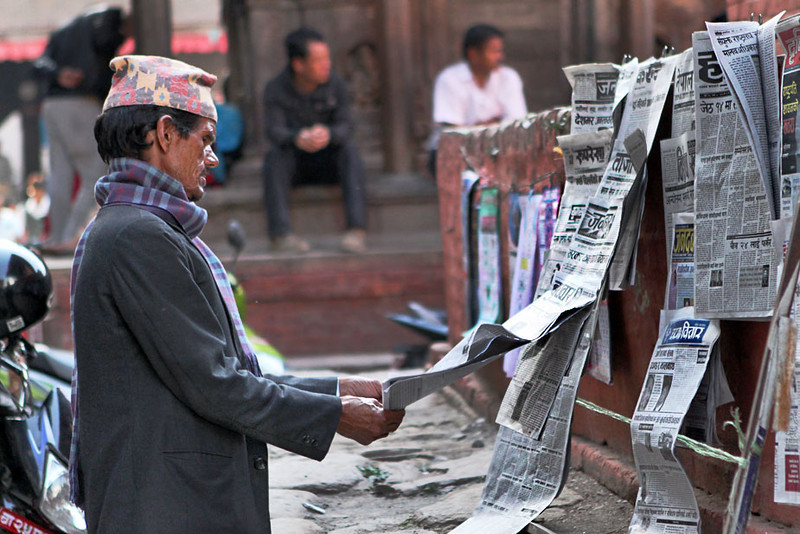Man reads the day's news in Durbar Square, Kathmandu, Nepal