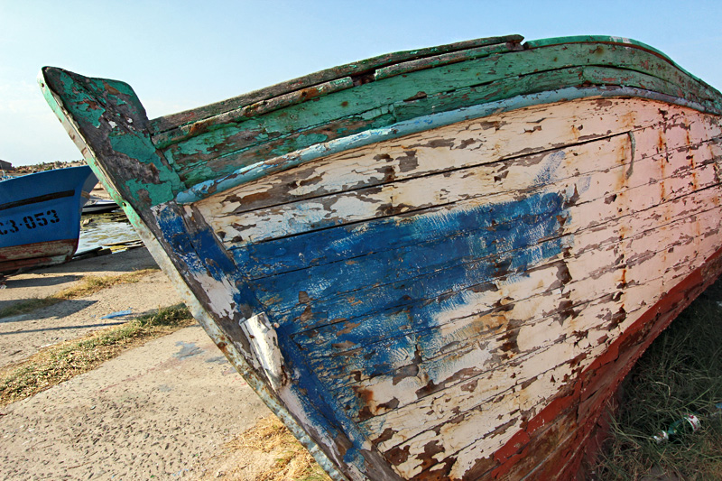 An old wooden fishing boat is beached in Sozopol, Bulgaria, awaiting restoration