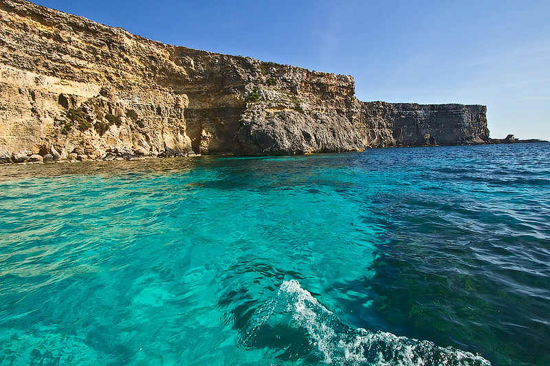 Sea cliffs rise vertically from exquisitely clear turquoise water surrounding the island of Comino in the Maltese Islands