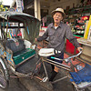 Trishaw driver poses for photo at a local produce market in Chiang Mai, Thailand