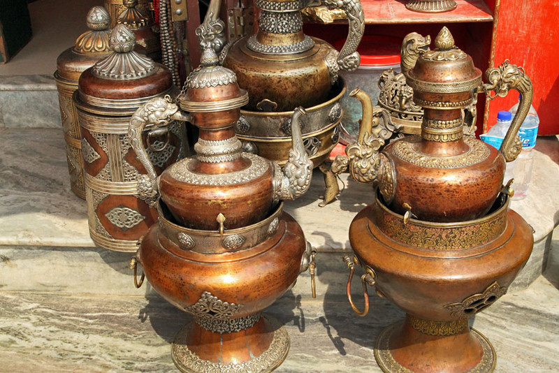 Ornate copper serving vessels in front of a store at Boudhanath Buddhist Temple in Kathmandu, Nepal