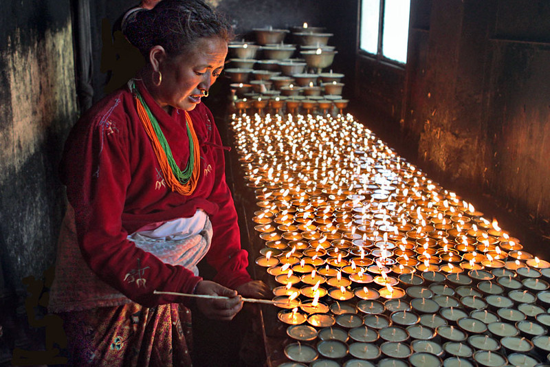 Tibetan woman lights butter candles to pray for her ancestors at Swayambhu (Monkey) Temple in Kathmandu, Nepal
