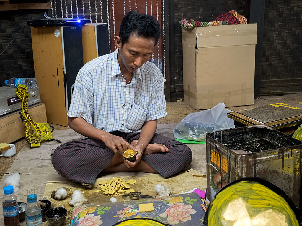 In Bagan, Myanmar, man applies gold foil to the inside of a lacquerware cup