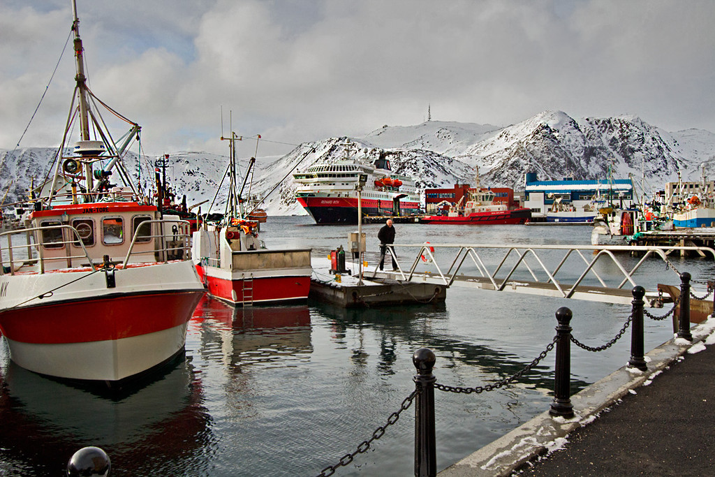 In the white landscape of Honningsvag, Norway, boats in the harbor provide a splash of color