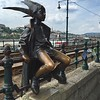 Bronze jester perches on the tramway railing along the Duna Corso, the Danube River promenade in Budapest, Hungary