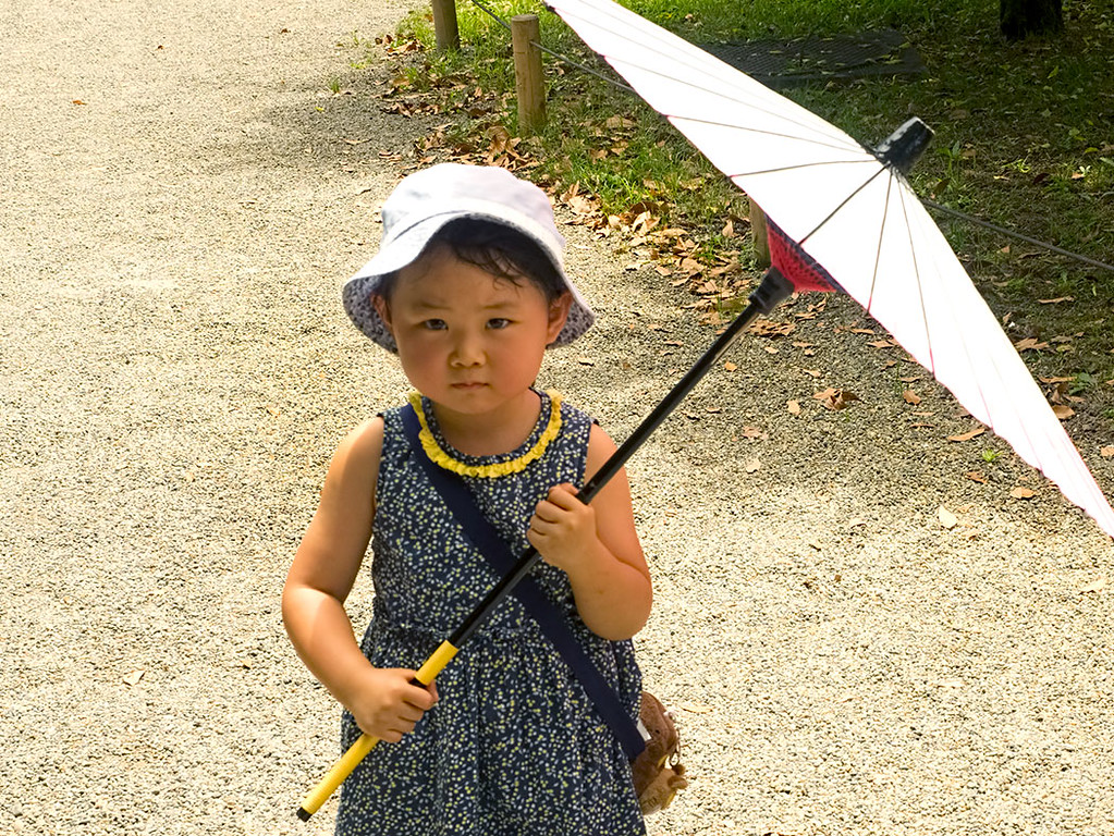 Japanese girl with umbrella shelters from the sun in Hama-rikyu Gardens in Tokyo, Japan