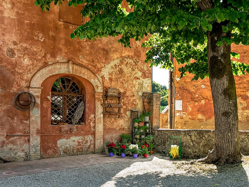 Centuries old palace at Montestigliano luxury holiday farm in Tuscany, Italy, is drenched in shades of gold and burnt orange under the setting sun