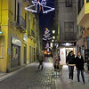 Christmas decorations hang above pedestrian shopping street in Figueres, Spain