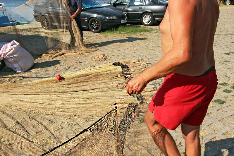 Fishermen mend nets by hand on the wharf in Sozopol, Bulgaria