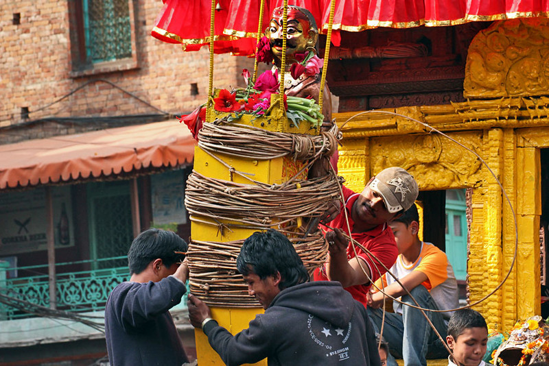 Devotees tie idol of god onto a wooden chariot that will be used in a tug-of-war during the Bisket Jatra Festival in Bhaktapur, Nepal