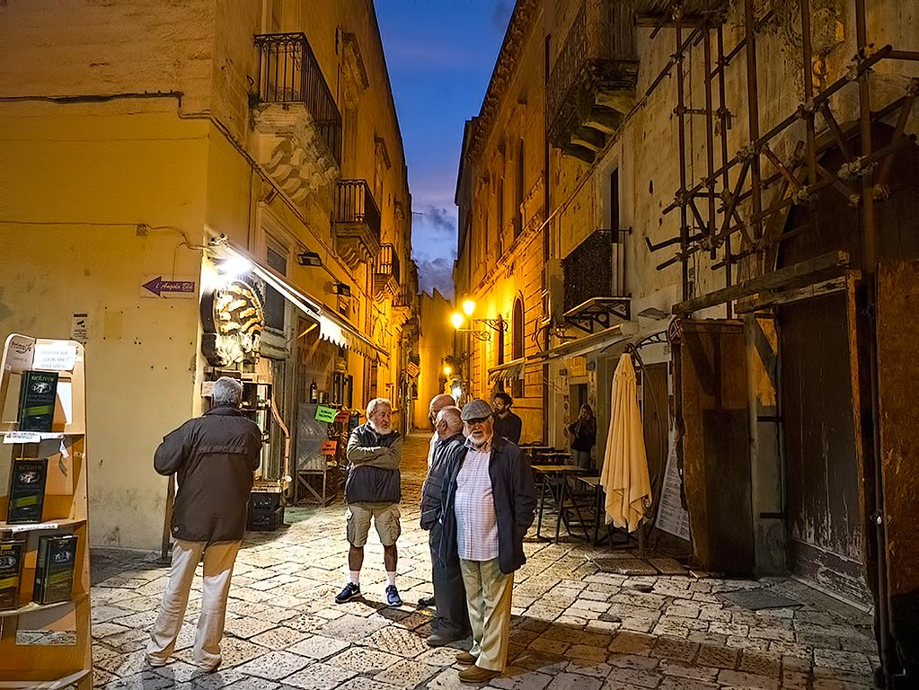 Local men gather to share the day's news in the historic center of Gallipoli, Italy, visited during my Flavours Holidays cooking holiday