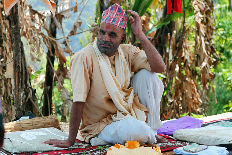 Priest relaxes between ceremonies at a puja for a deceased family member in Nayagaon, Nepal