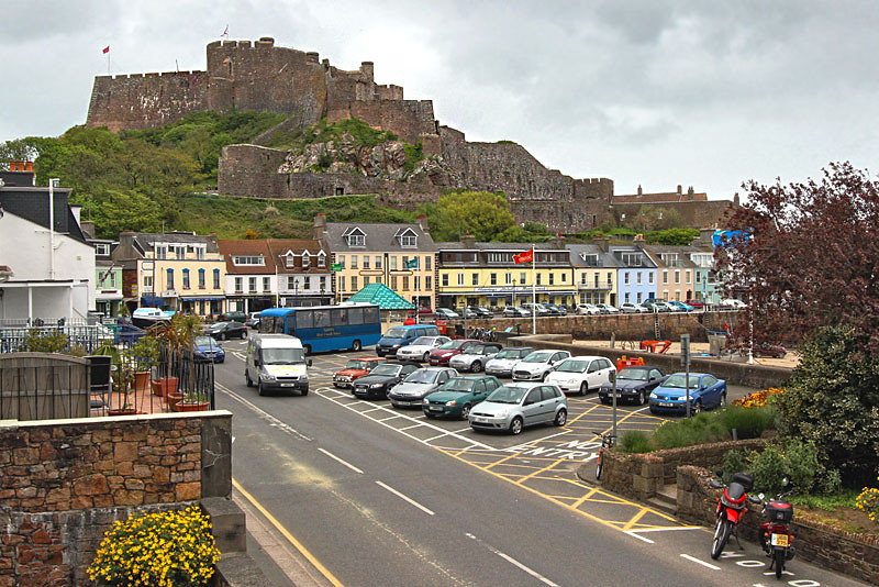 Gorey Castle looms above colorful homes and shops on Jersey in the British Channel Islands