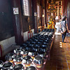 To earn merit, Buddhists drop a coin in each of 108 bowls at Wat Phan Tao in Chiang Mai, Thailand