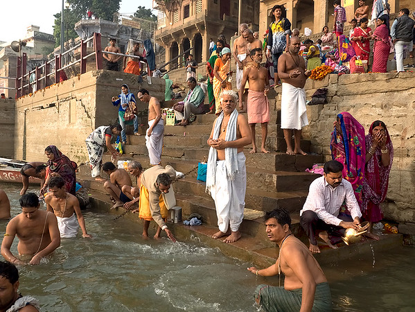 Worshipers at the ghats of Varanasi, India. They flock to the shores of the Holy Ganges River each morning at dawn to bathe in and drink from its waters.