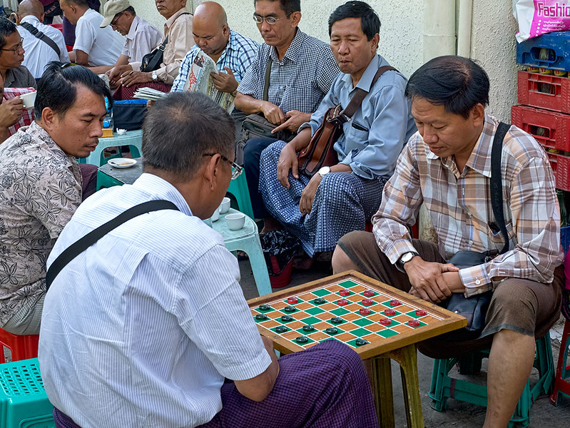 Afternoon break for tea and checkers in Myanmar. Squatting on low plastic stools set out on the streets around the Scott Market in Yangon, they seem oblivious to the cars and motorcycles speeding by with just inches to spare.