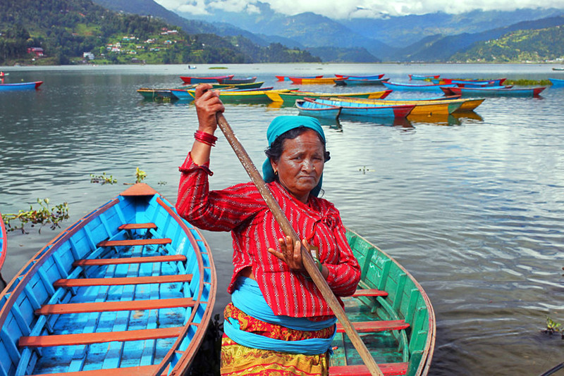 Boatwoman ferries worshipers to Barahi Temple on a small island in Phewa Lake, Pokhara, Nepal