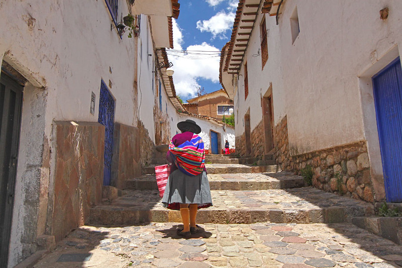 Quichua woman slowly makes her way up narrow streets in the San Blas neighborhood of Cusco, Peru