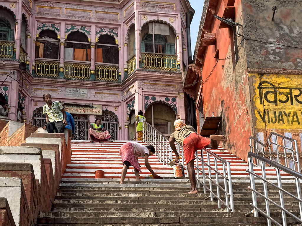Workers paint the shared steps between Vijayana Garam Ghat and Kedar Ghat in Varanasi, India