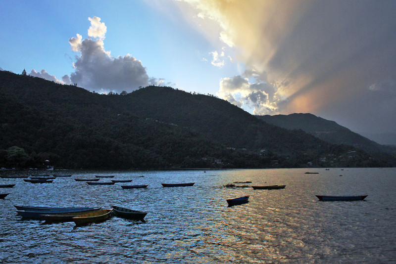Setting sun lights up the skies over Phewa Lake in Pokhara, Nepal