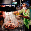 Strings of sausage balls simmer on a barbeque during the Saturday night market in Chiang Mai, Thailand