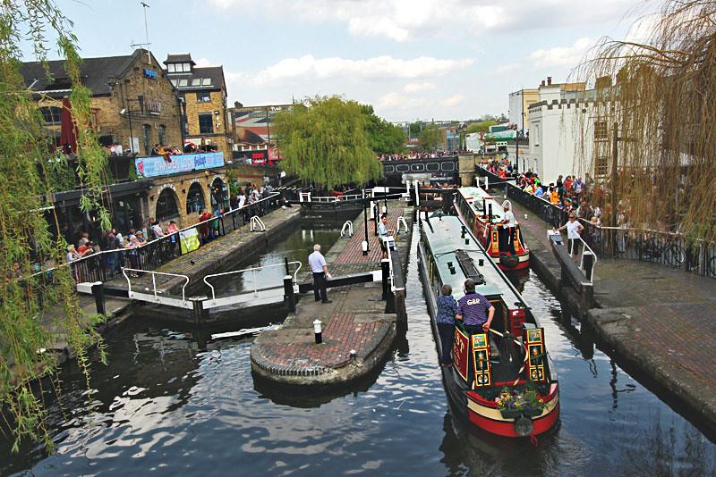 Long river boats negotiate a series of three locks at Camden, London