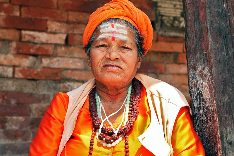 Old woman strikes a pose at the Pashupatinath Temple in Kathmandu, Nepal