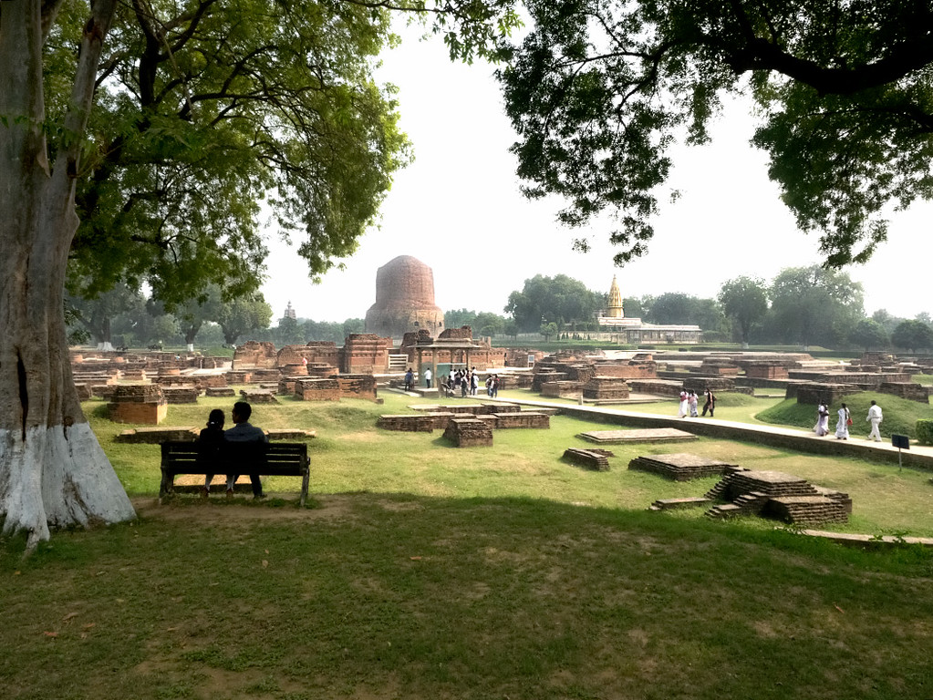 Archeological excavations of ancient Buddhist monasteries in Sarnath, India. Gautama Buddha first taught the Dharma here.  The three structures in the distance, from left to right, are the Main Temple, the Dhamekh Stupa, and the Jain Temple.