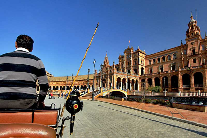 Horse-drawn carriage carries tourists past Plaza de Espana in Seville, Spain
