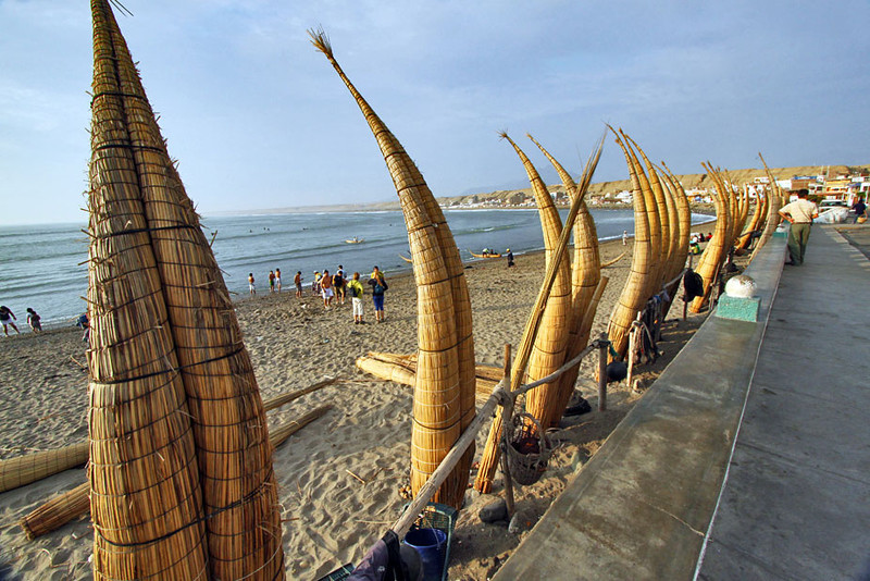 Hand-woven reed rafts stand ready to rent in the small beach village of Huanchaco, near Trujillo, Peru