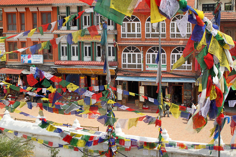 Prayer flags cascading from Boudhanath frame surrounding buildings, Kathmandu, Nepal