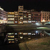 Building lights reflect in the Onyar River on a winter night in Girona, Spain