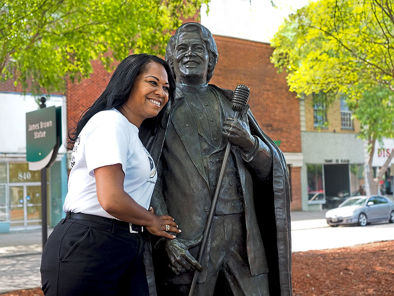 Deanna Brown-Thomas poses in downtown Augusta with the statue of James Brown, her father