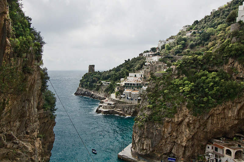 Old stone tower guards the entrance to this aquamarine cove on the Amalfi Coast in Italy