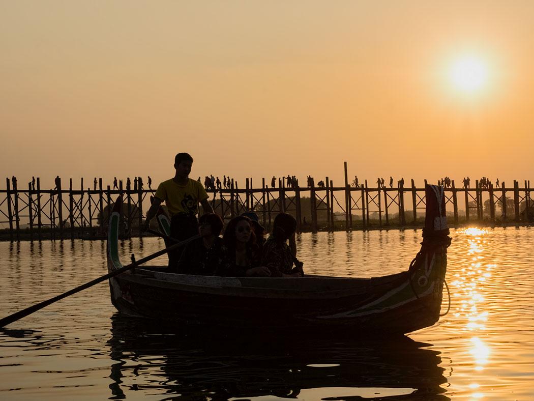 In Mandalay, Myanmar, sun sets behind U Bein Bridge, said to be the longest and oldest teak bridge in the world