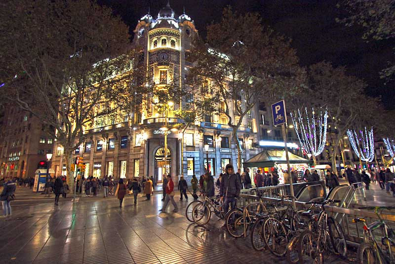 Night scene on La Rambla, a wide pedestrian walkway in Barcelona, Spain