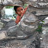Boy peeks from behind giant carvings lining a bridge at Angkor Wat ruins in Cambodia