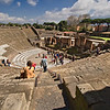 The Great Theater at Pompeii, which could seat up to 5,000 spectators, dates from the end of the 3rd century BCE. It was built in the Greek style, which took advantage of the natural slope of the terrain and had a U-shaped orchestra. During performances of comedies and tragedies, long lengths of colored cloth were strung over the seating to provide shade for the audience.