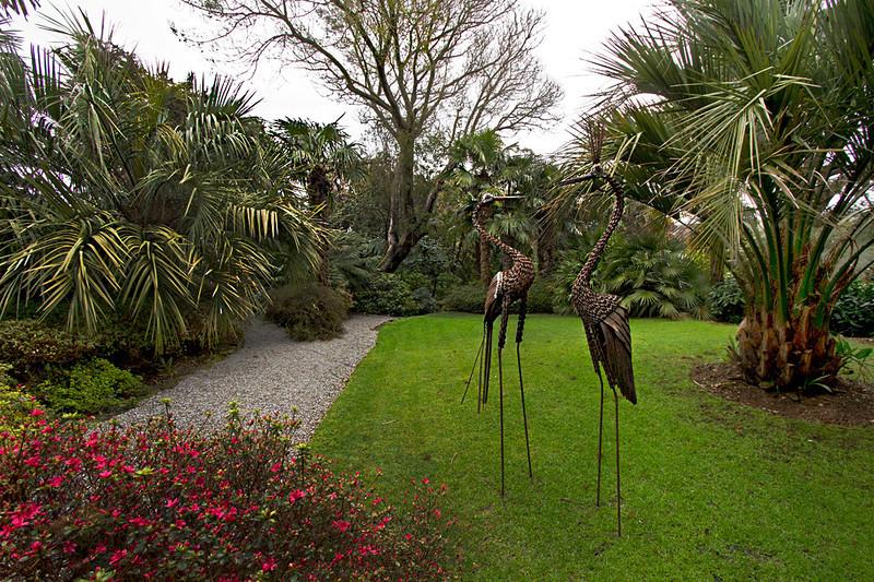Bronze flamingos grace a lush expanse of lawn at Lamorran House Gardens in Cornwall, England