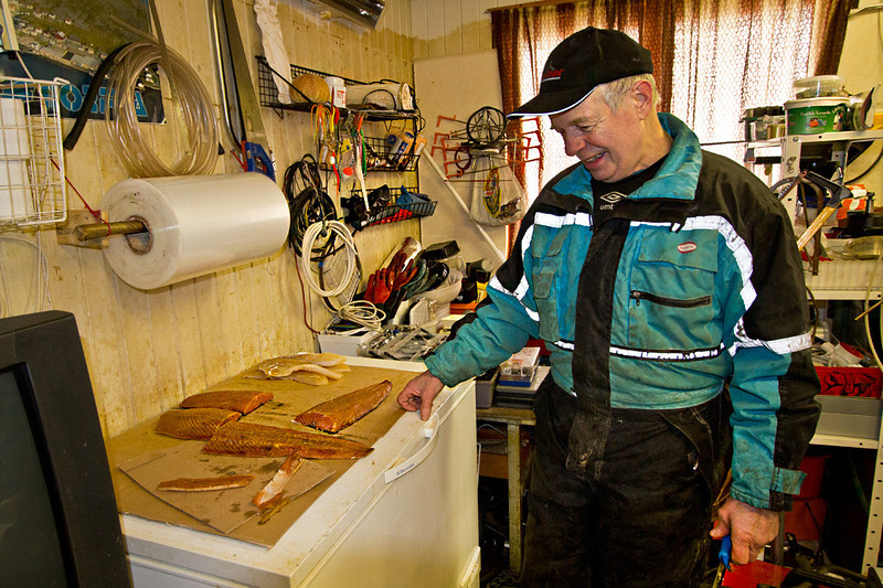 Alfred, a fisherman in the town of Honningsvag, Norway, offers me fresh smoked salmon