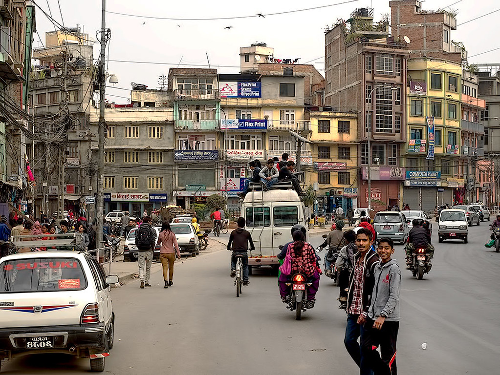 Typical street scene in Kathmandu, Nepal, with people riding on the roof of overloaded van bus