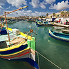 Fishing boats in the harbor at Marsaxlokk , Malta are painted in rainbow colors