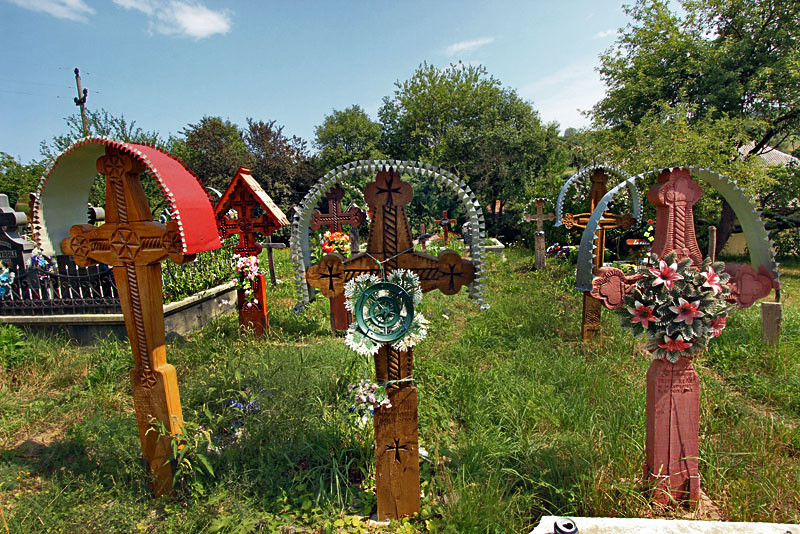 Unique hand-carved crosses with decorative tin roofs stand at the head of graves in Breb, Maramures in northern Romania