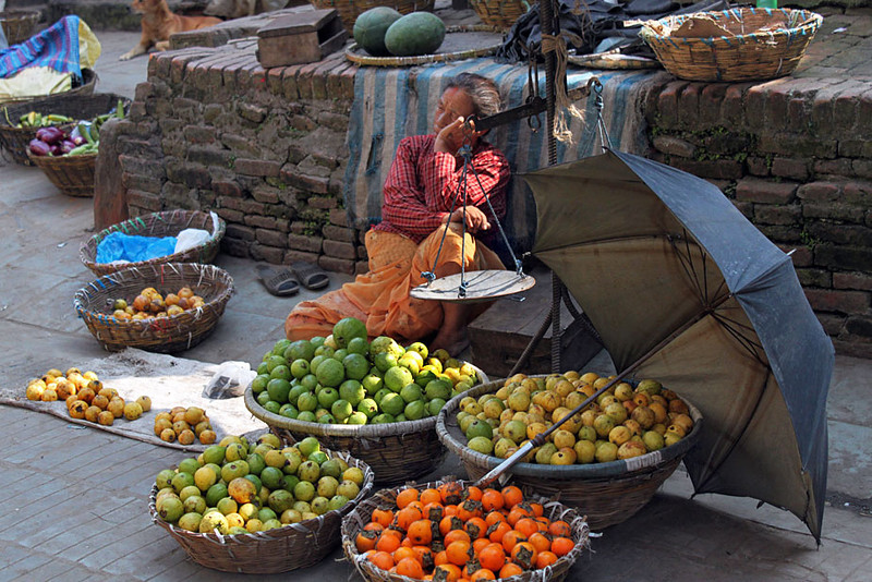 Fruit seller succumbs to sleep in late afternoon sun, Durbar Square, Kathmandu, Nepal