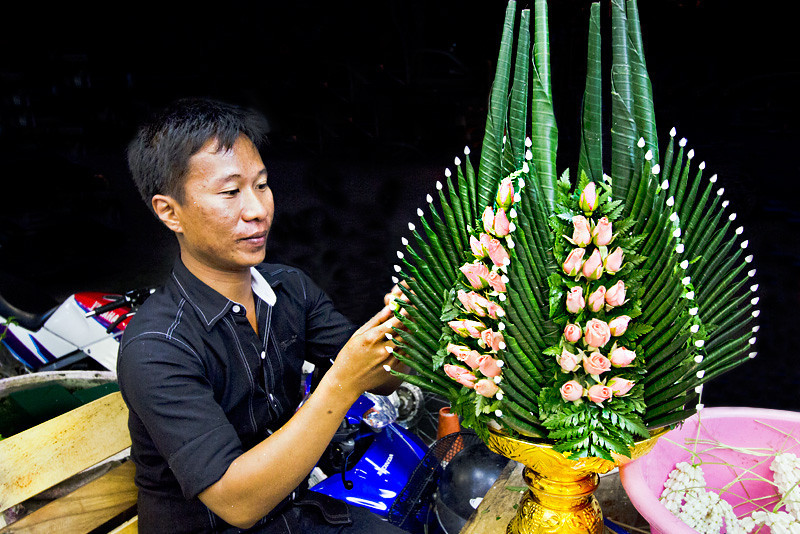 Artist creates a floral design from rosebuds and banana leaves in the Thai tradition in Chiang Mai