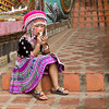 Hill tribe girl in traditional costume sits on the stairway leading to Doi Suthep Temple in Chiang Mai, Thailand