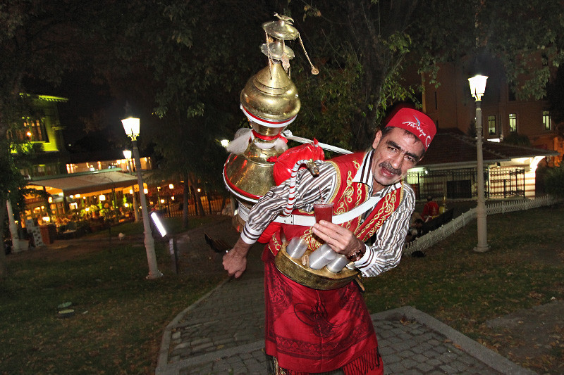 Istanbul vendor in traditional costume pours drink known as Sherbet from large vessel carried on his back