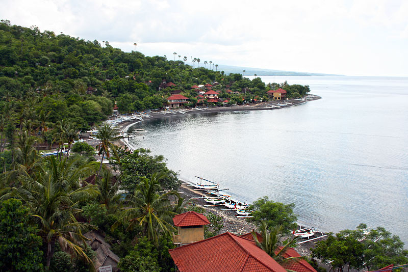 Hand-hewn wooden boats line the black beach in Amed, Bali